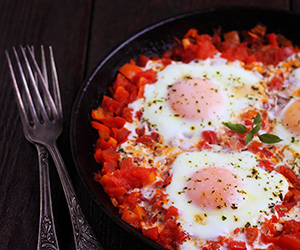 scrambled eggs with herbs, tomatoes and peppers. shakshuka